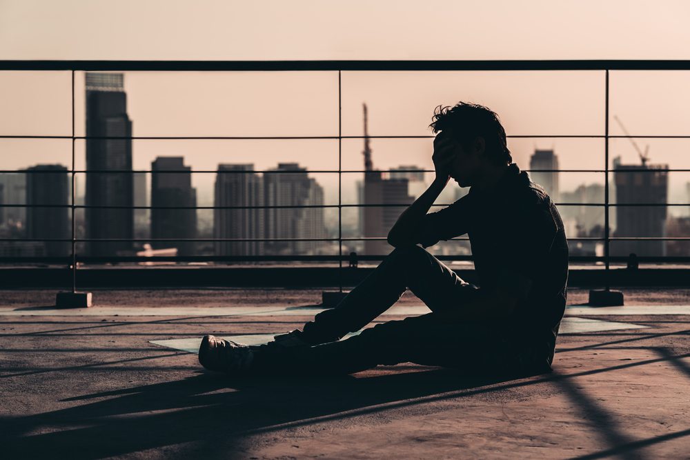 Thinking about rehab, sad man sitting on a city rooftop