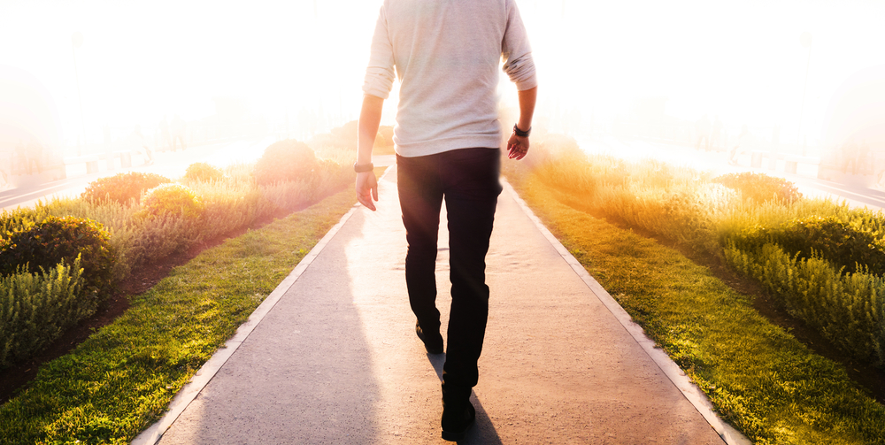 man walking on a path into a sunset