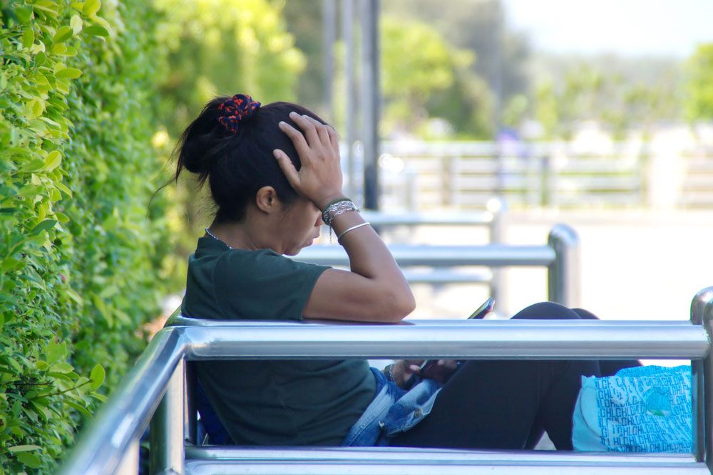 woman sitting on a bench and feeling shame